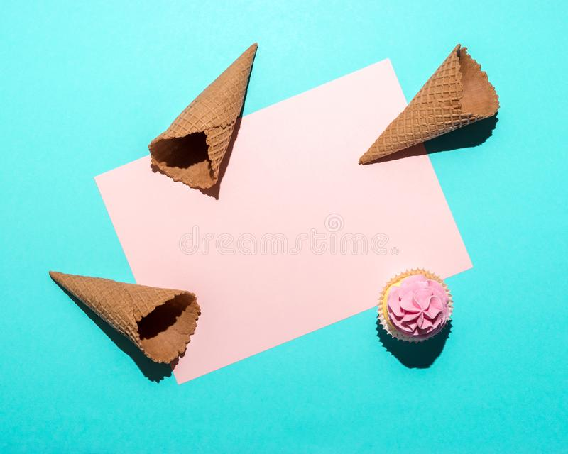 Cupcake and ice cream cones on bright blue background. Minimal summer composition. Flat lay royalty free stock image