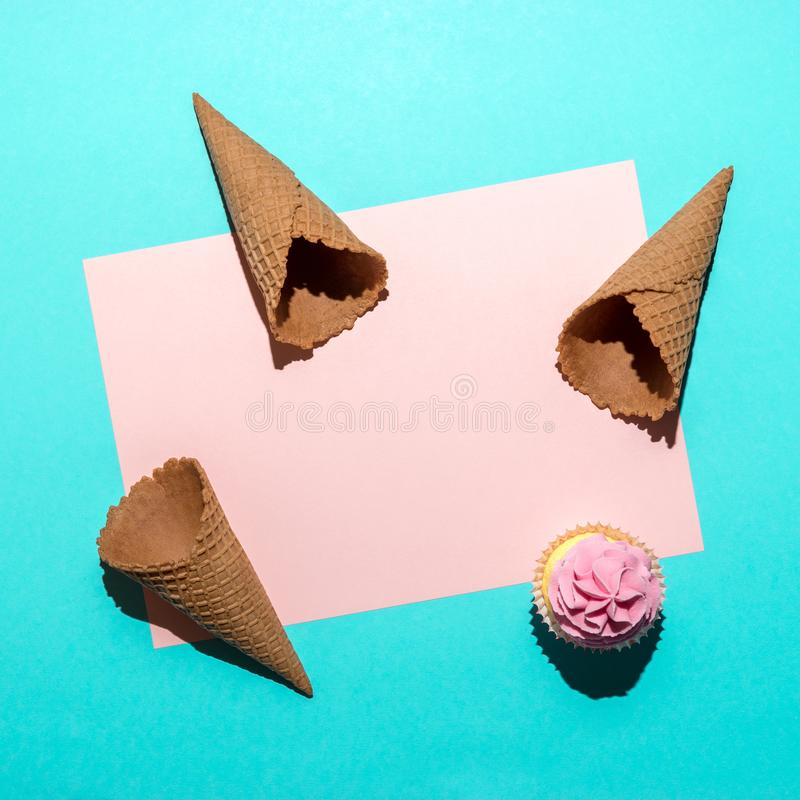 Cupcake and ice cream cones on bright blue background. Minimal summer composition. Flat lay stock photos