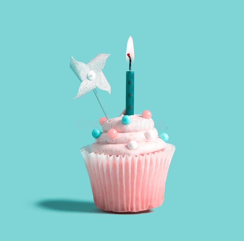 Cupcake met een aangestoken kaars stock fotografie