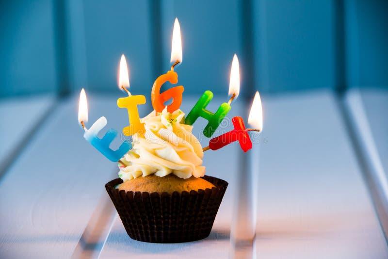 Cupcake met kaarsen voor 8 - achtste verjaardag stock afbeeldingen