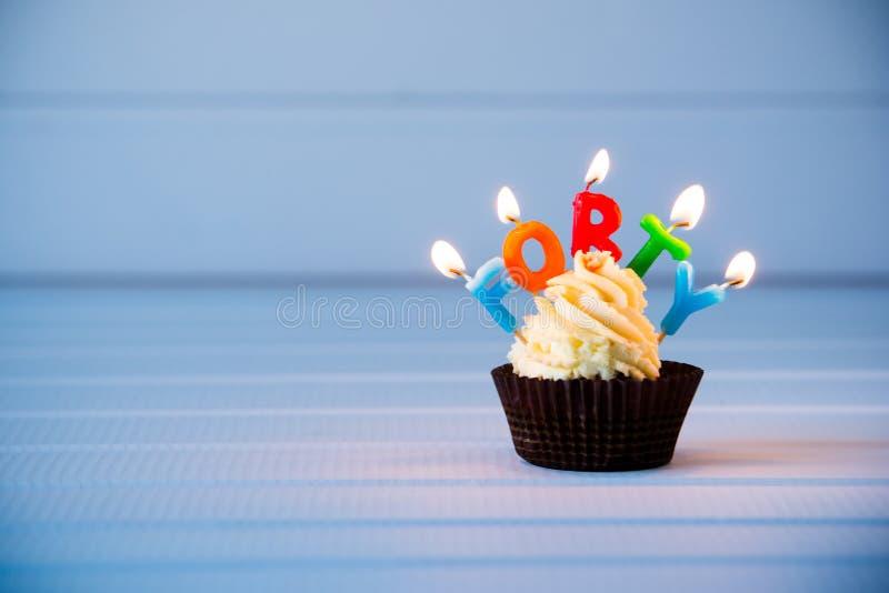 Cupcake met kaarsen voor 40 - veertigste verjaardag stock afbeelding