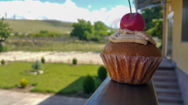 Cupcake met room en kers, op de achtergrond van de tuin naast het huis stock afbeeldingen