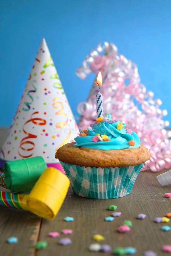 Cupcake met sterkaarsen en verjaardagshats stock fotografie