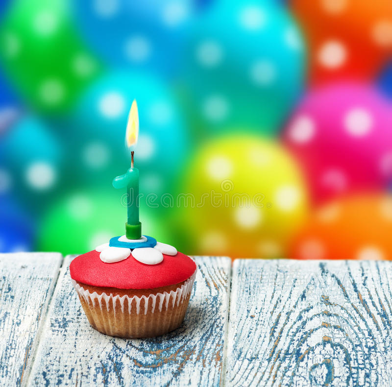Cupcake with number one on the background of balloons stock photography