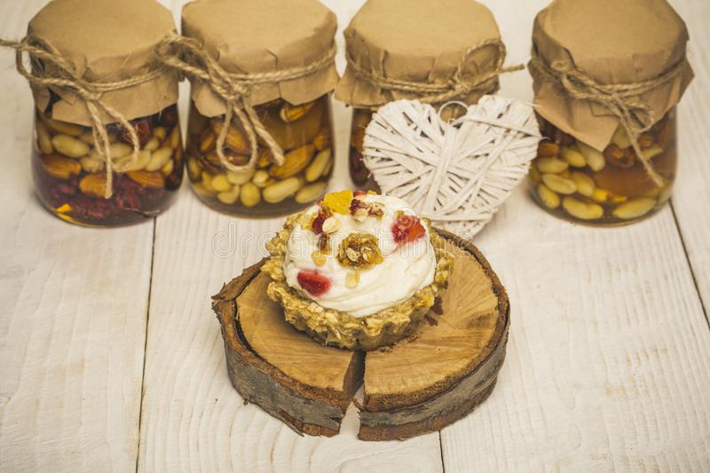 Cupcake, nuts in glass jars and heart on wooden background stock images