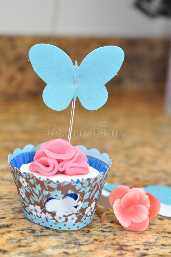 Cupcake with Pink Flower and Butterfly. Cupcake decorated for Spring with pink frosting flower and blue butterfly stock photo