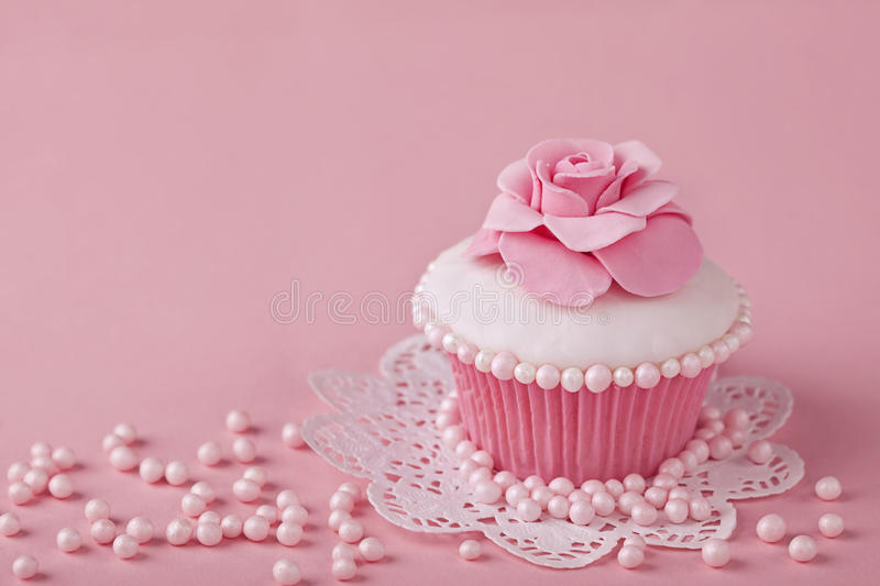 Cupcake with pink flowers royalty free stock photography