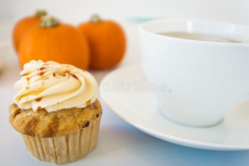 Cupcake and pumpkins and tea. Pumpkin caramel cupcake with cream cheese swirl and baby pumpkin and cup of hot tea royalty free stock photos