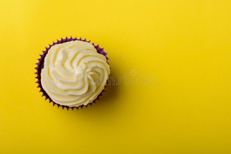 Cupcake in purpere omslag op gele achtergrond minimalism Hoogste mening met exemplaarruimte stock foto