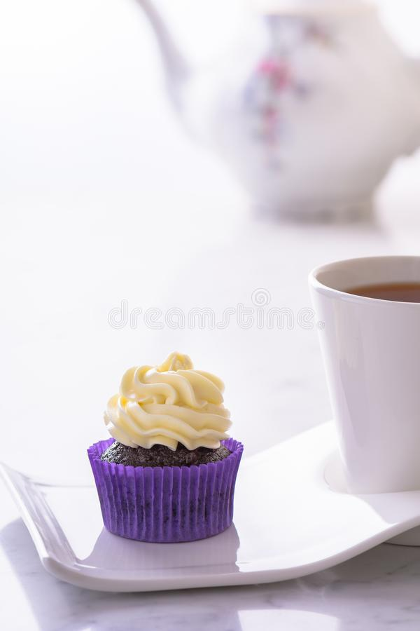 Cupcake in purple wrap and a cup of tea on white natural marble table top with copy space. Cupcake in purple wrap and cup of tea on white natural marble table stock photo