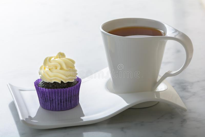 Cupcake in purple wrap and a cup of tea on white natural marble table top with copy space. Cupcake in purple wrap and cup of tea on white natural marble table royalty free stock images