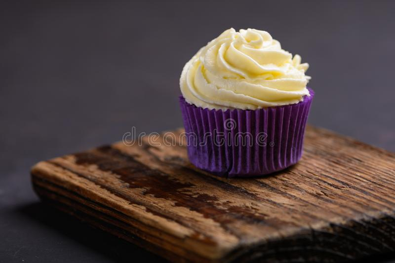Cupcake in purple wrap on wooden board on dark stone table. Minimal concept. Copy space stock image