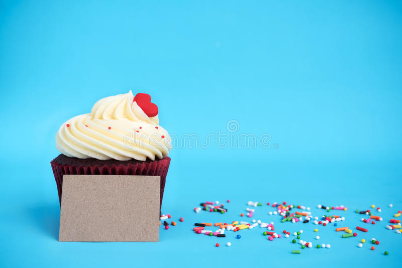 Cupcake with red heart, colorful sprinkles and brown note. Over blue background with copy space stock photography