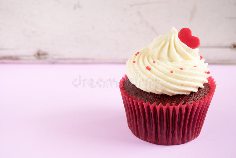 Cupcake with red heart. Over vintage wooden background with copy space, Gift for valentine, wedding birthday and anniversary day stock images