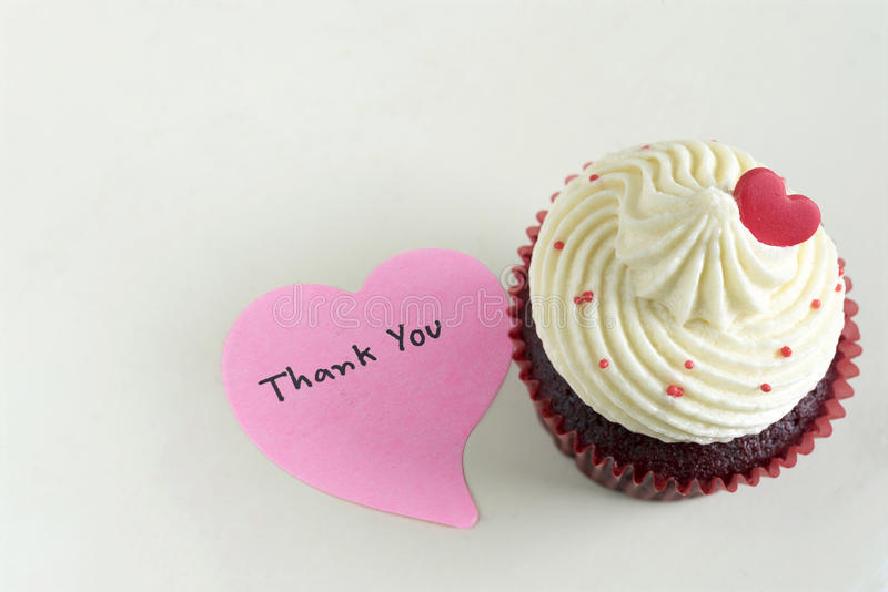 Cupcake with red heart and thank you massage. Cupcake with red heart and pink sticky note with handwriting words thank you with copy space on off white table stock images