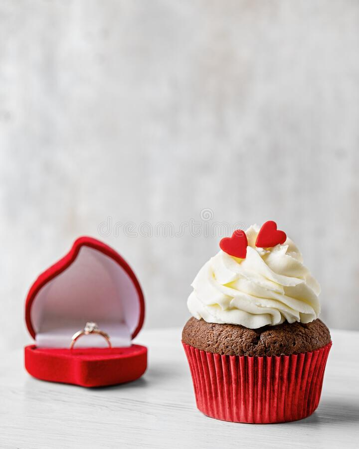 Cupcake in the red paper wrapper with red hearts on the top and with an engagement ring. Greeting with Valentine`s Day. Cupcake in the red paper wrapper with red royalty free stock photos