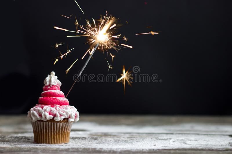Cupcake with red swirl frosting and sparkler, christmas cupcake. Decoration stock photography