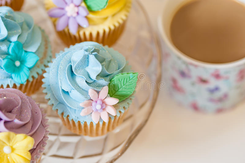 Cupcake selection in pastel colors. With cup of tea stock photography