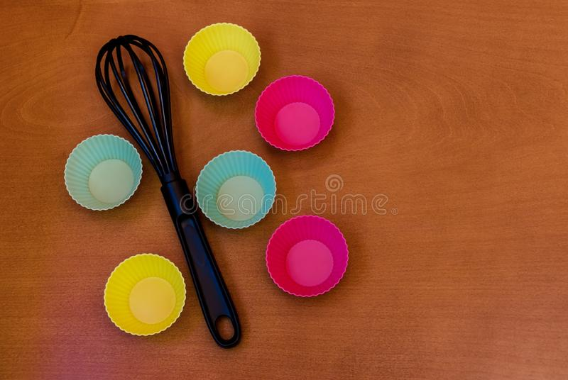 Cupcake silicon baking cups and whisk over wooden background. With copy space stock images