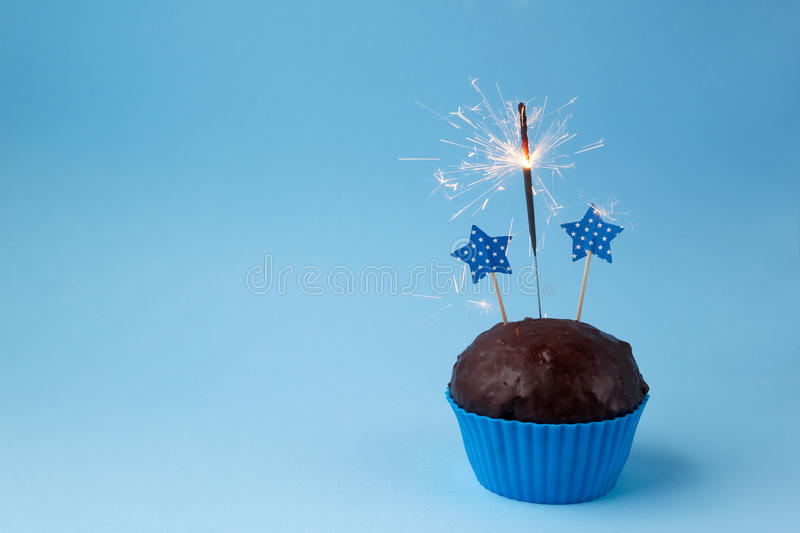 Cupcake with sparkler against a blue background royalty free stock images