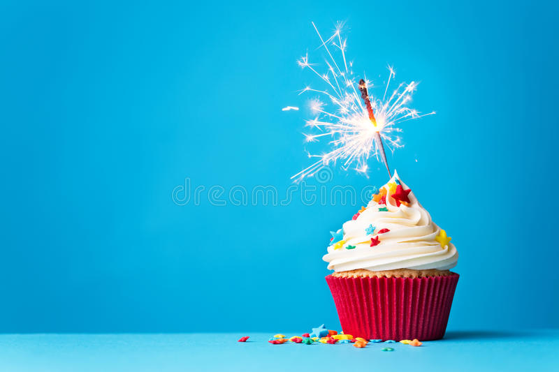 Cupcake with sparkler on blue royalty free stock image