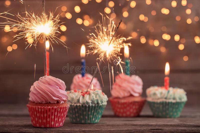 Cupcake with sparkler on wooden background stock image