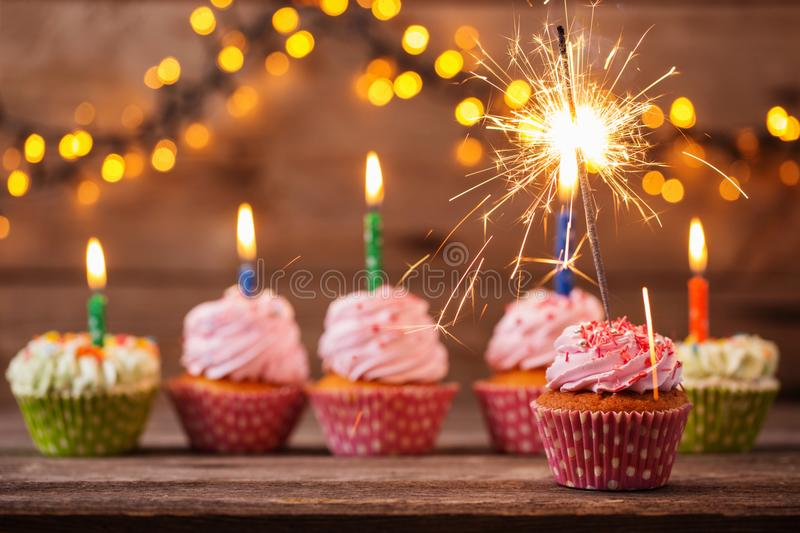 Cupcake with sparkler on old wooden background royalty free stock images