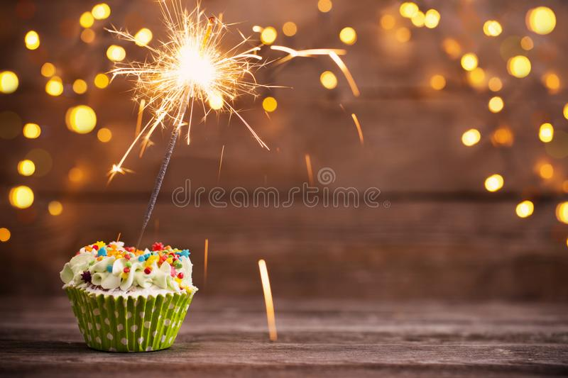Cupcake with sparkler on old wooden background royalty free stock photos