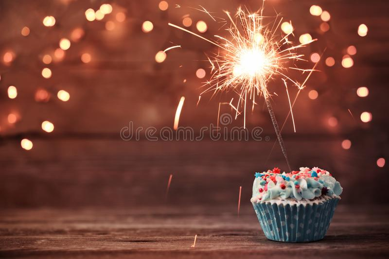 Cupcake with sparkler on old wooden background stock photos