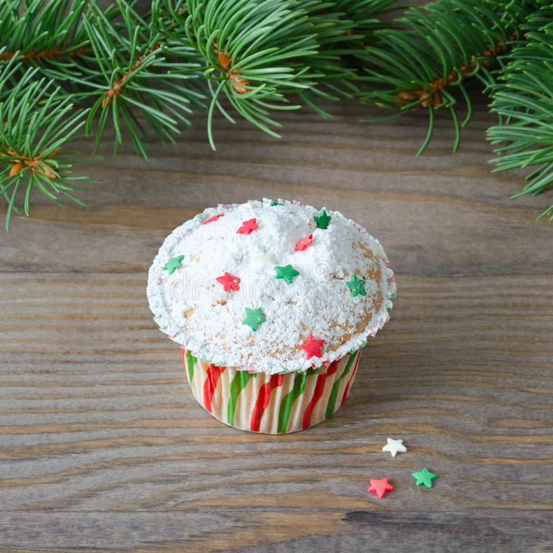 Cupcake with star decoration and christmas tree on wooden background. stock photography