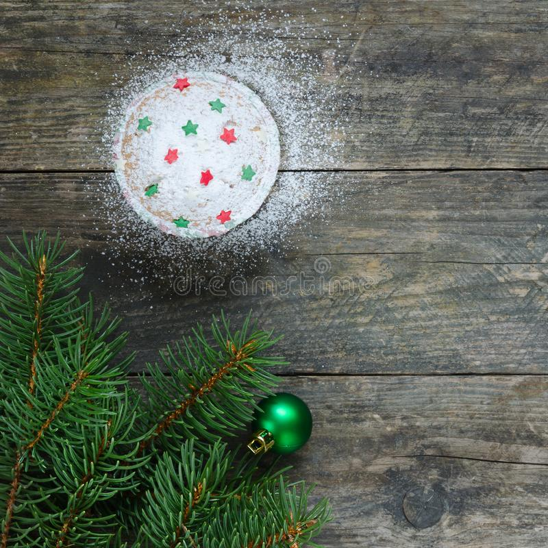 Cupcake with star decoration. Green christmas ball and christmas tree on old wooden background. Christmas card. Copy space composition stock photography