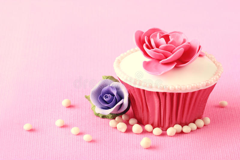 Cupcake. Sweet Cupcake with flower decoration in pink royalty free stock photography