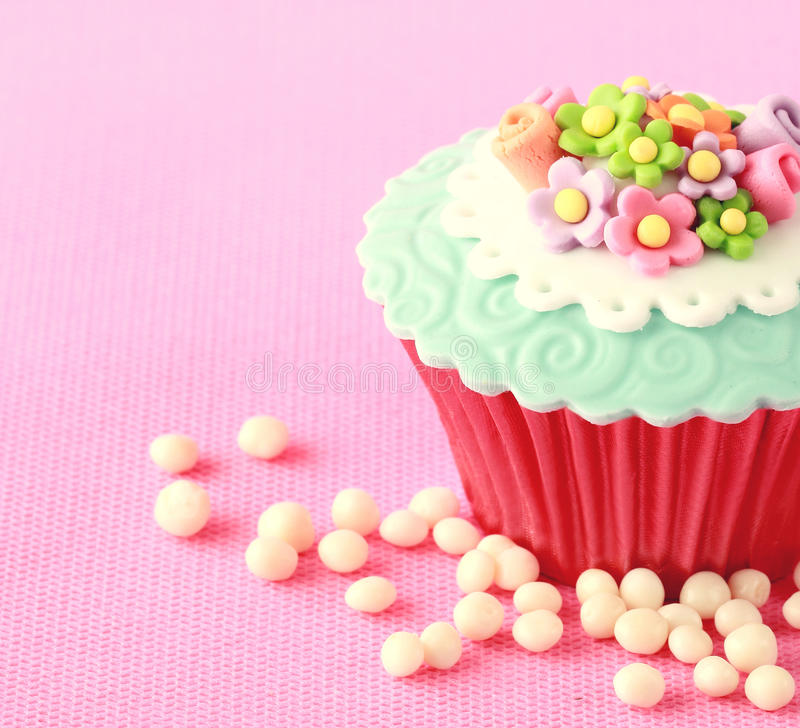 Cupcake. Sweet Cupcake with flower decoration in pink royalty free stock image
