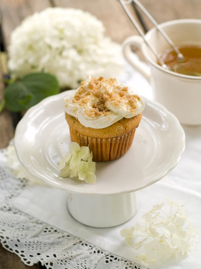 Cupcake. With swirl icing and cup of tea, selective focus stock image