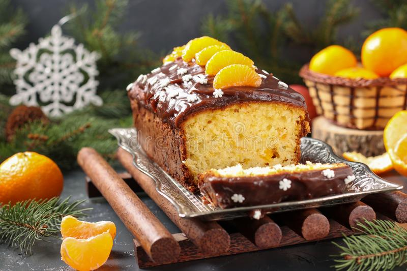 Cupcake with tangerines, covered with chocolate glaze is located on the New Year`s background, Festive still life. Cupcake with tangerines, covered with royalty free stock photos