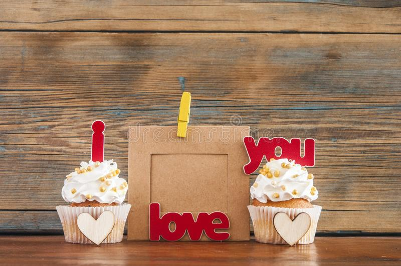 Cupcake and word Love on wooden table. royalty free stock photos
