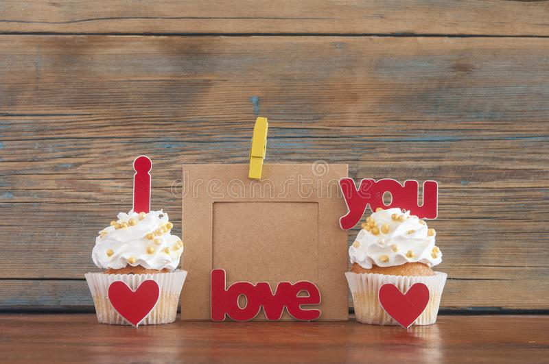 Cupcake and word Love on wooden table. royalty free stock images