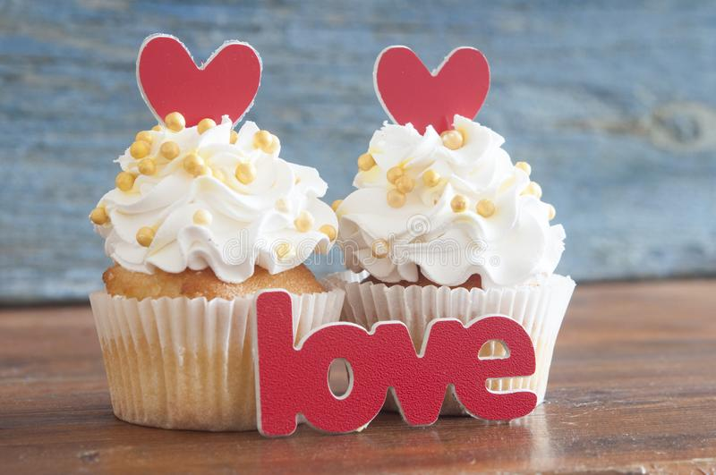 Cupcake and word Love on wooden table. stock photos