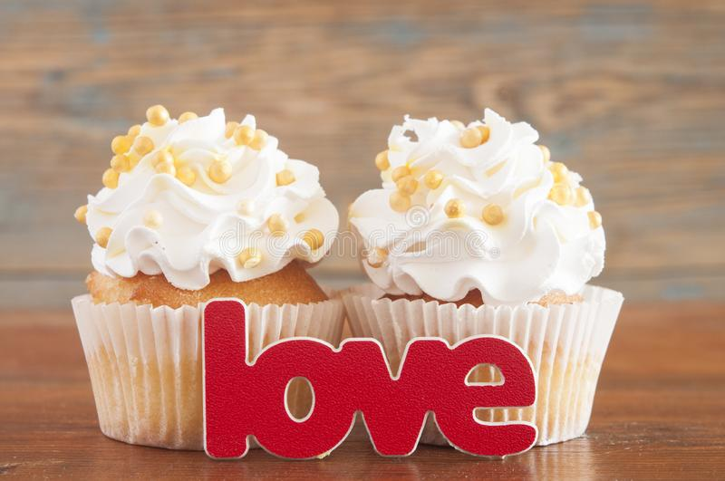 Cupcake and word Love on wooden table. stock images