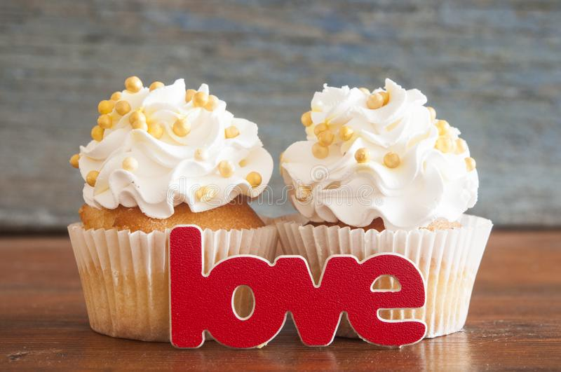 Cupcake and word Love on wooden table. royalty free stock image