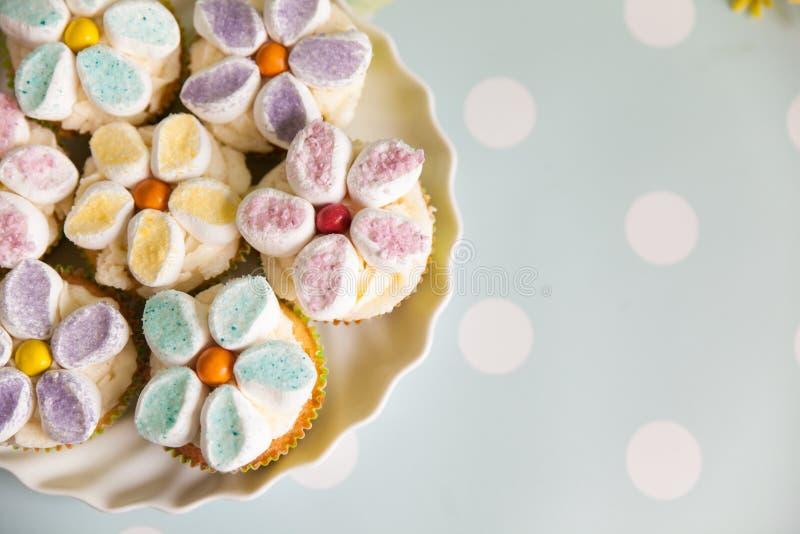 Cupcakes που διακοσμείται με τα βουτύρου λουλούδια κρέμας και marshmallow στοκ εικόνα