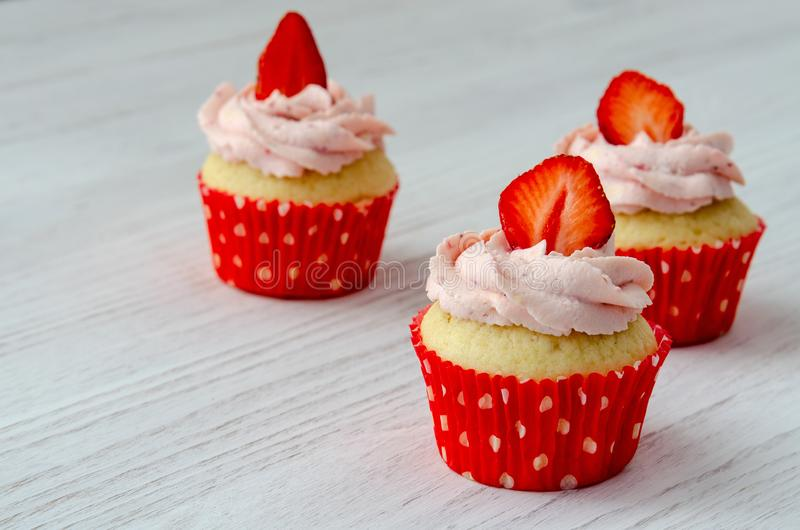 Cupcakes με τη διακόσμηση φραουλών σε ένα άσπρο ξύλινο υπόβαθρο στοκ φωτογραφία με δικαίωμα ελεύθερης χρήσης