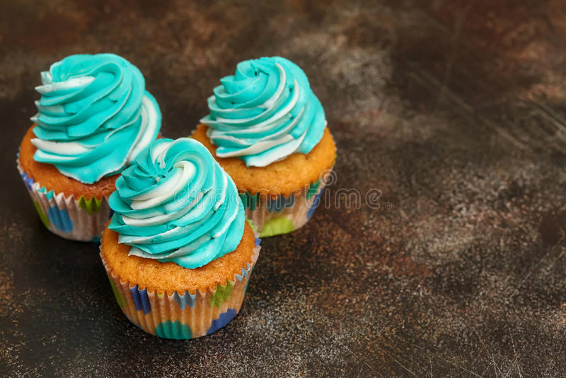 Cupcakes με το τυρκουάζ και άσπρο buttercream που παγώνει στο καφετί υπόβαθρο στοκ φωτογραφίες με δικαίωμα ελεύθερης χρήσης