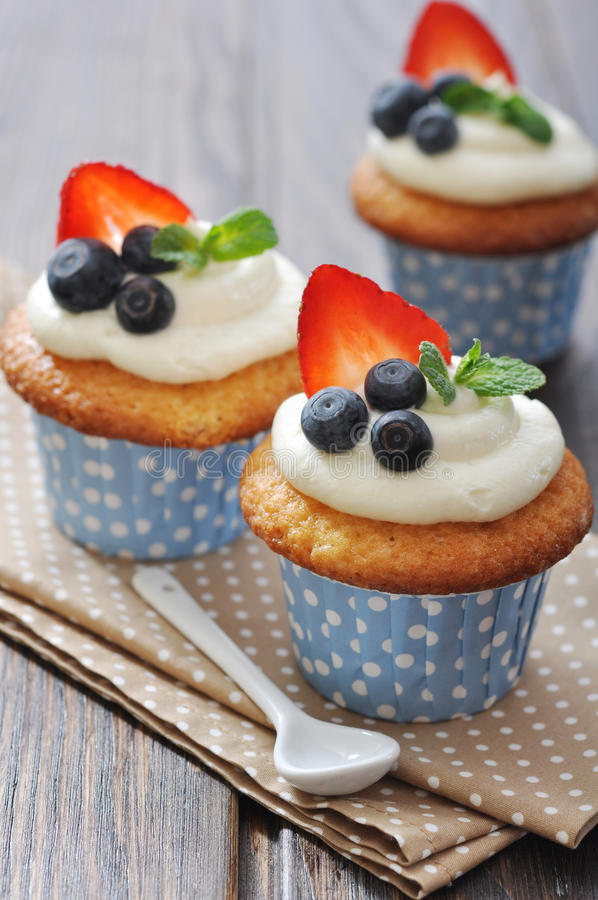 Cupcakes που διακοσμείται με τα φρέσκα μούρα στοκ εικόνα