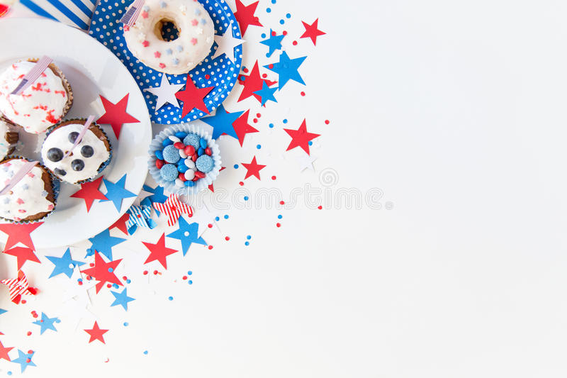 Cupcakes with american flags on independence day. Independence day, celebration, patriotism and holidays concept - close up of glazed cupcakes or muffins stock photo