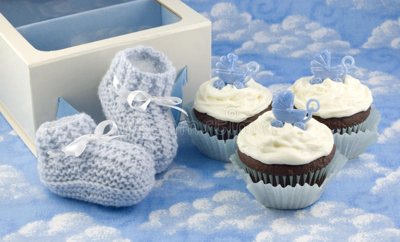 Cupcakes and Baby Booties for Boy. A pair of crocheted blue baby booties, a gift box and delicious chocolate cupcakes with vanilla frosted, horizontal with copy royalty free stock photography