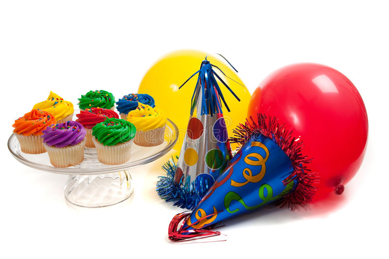 Cupcakes, balloons and party hats stock photography