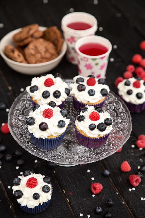 Cupcakes with berry for a sweet holiday buffet. Delicious cupcakes with berry for a sweet holiday buffet royalty free stock images