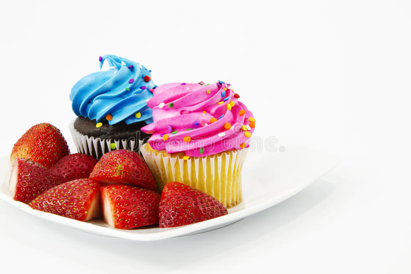 Cupcakes with Blue and Pink Frostings. Two cupcakes, one with blue frosting and one with pink frosting, are garnished with sliced strawberries royalty free stock photos