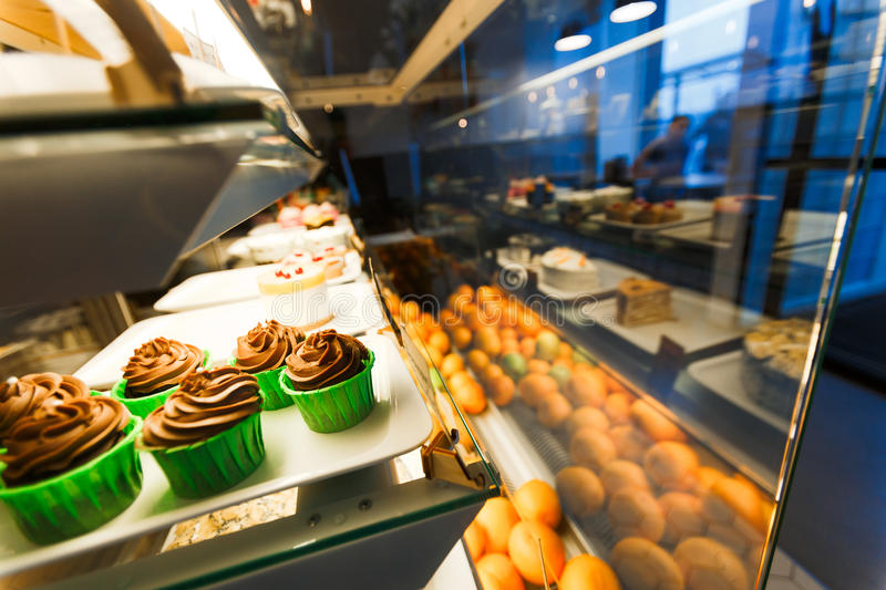 Cupcakes in cafeteria. Chocolate cupcakes and tangerines in display window in cafeteria royalty free stock image